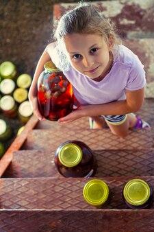 女の子はセラーから自家製イチゴのコンポートの大きなガラスの瓶を取る