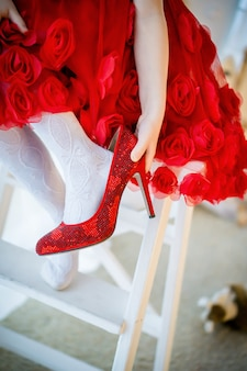 Девушка берет мамины туфли, красное платье и туфли на высоком каблуке