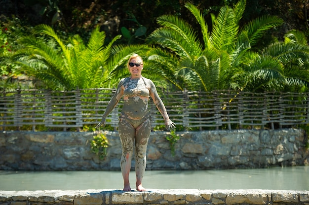 A girl takes a mud bath at a resort in turkey.health improvement in therapeutic mud.