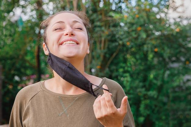 소녀는 야외에서 얼굴에서 보호 마스크를 벗습니다. 예방 접종 후 마스크를 제거하는 젊은 여성