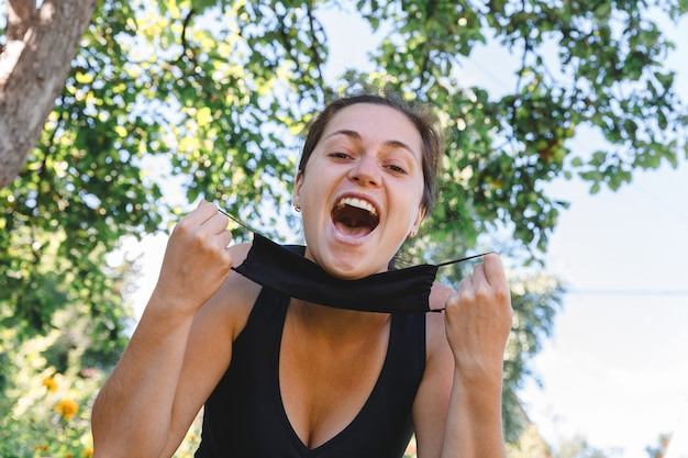소녀는 야외에서 보호 마스크를 벗다 예방 접종 후 웃고있는 마스크를 제거하는 젊은 여성