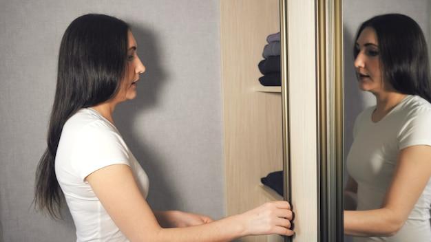 Девушка достает одежду из шерстяного свитера со шкафом.