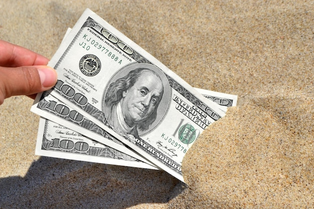 A girl takes out from the sand money notes of three hundred dollars.