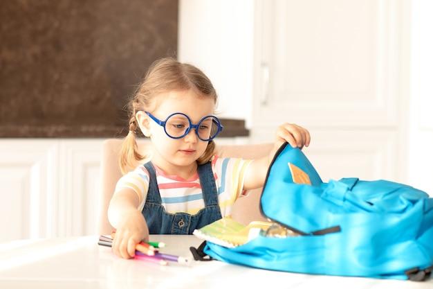 女の子はバックパックから学校の文房具を取り出し、日当たりの良いキッチンのテーブルで宿題をします学校に戻る