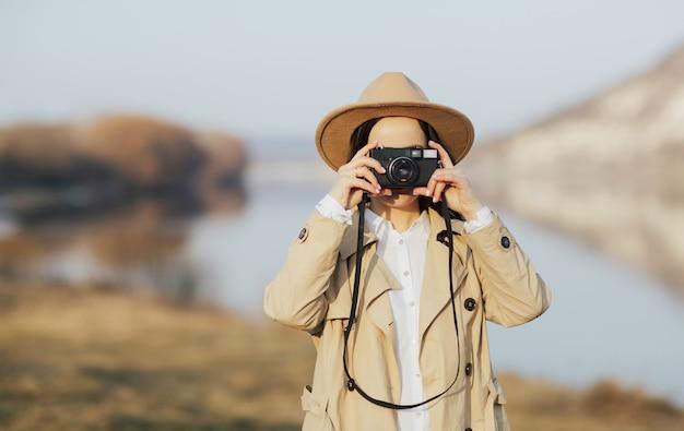 소녀는 산에서 레트로 카메라로 사진을 찍는다.