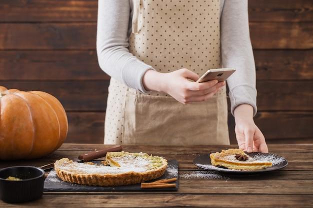 Девушка фотографирует тыквенный пирог на мобильный телефон