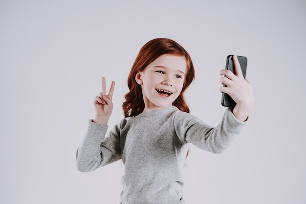 Girl takes pictures of herself on phone, show victory sign.