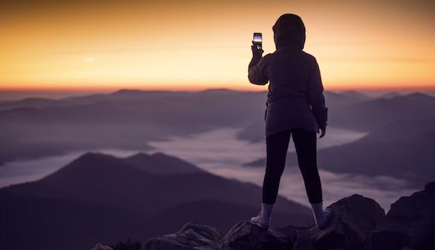 여자는 전화로 산에서 새벽의 사진을 찍는다.