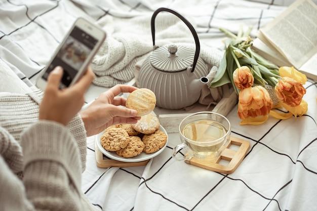 Una ragazza scatta foto sul telefono di una composizione primaverile con tè, biscotti e tulipani a letto