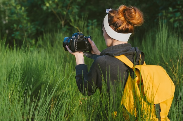 The girl takes pictures with a slr camera in the forest. against the backdrop of beautiful greenery.