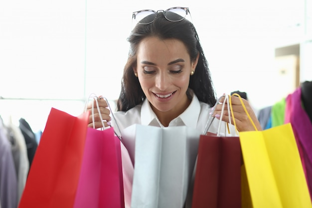 여자는 부티크 쇼핑에서 즐거움을 가져옵니다.