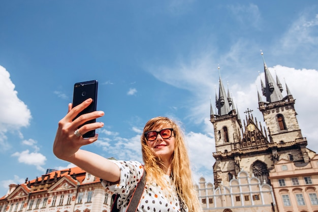 A girl takes a selfie on the background of the tyn church. photo on the phone in prague. beautiful young lady traveling in prague. happy woman tourist take a selfie.