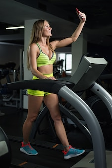 Girl takes a selfie in the gym, woman is photographed on the treadmill