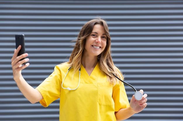 看護師として働きながら携帯電話で写真を撮る女の子