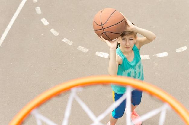 バスケットボールコートでゴールを狙う少女