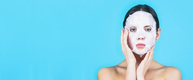 Девушка заботится о цвете кожи лица. уход за кожей и концепция красоты. увлажняющая маска. женщина, применяя маску листа на ее лице, на синем фоне. красивая женщина с маской.