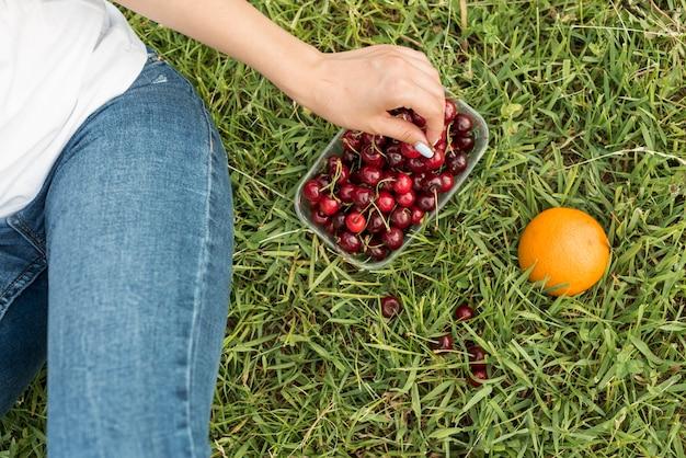 草の上に座ってチェリーを取っている女の子