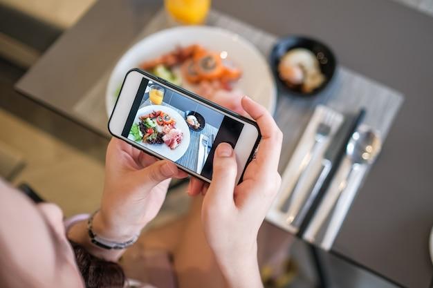 携帯電話のカメラで食べ物の写真を取っている女の子