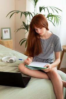 ベッドでメモを取る女の子ミディアムショット