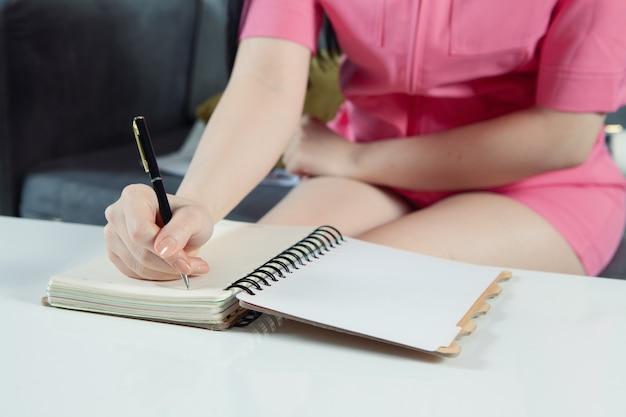 Девушка делает заметки на ноутбуке