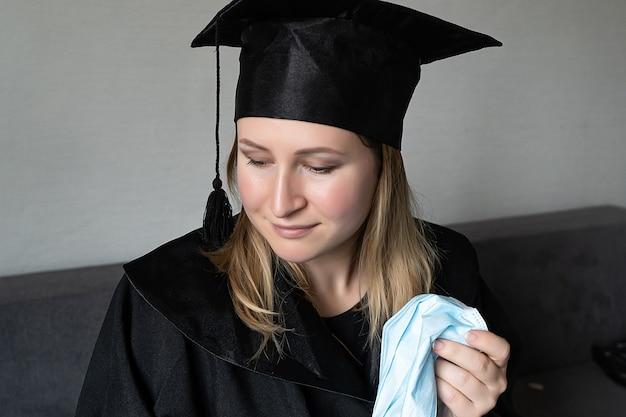 회색 배경에 졸업 모자를 쓰고 의료 마스크를 벗는 소녀