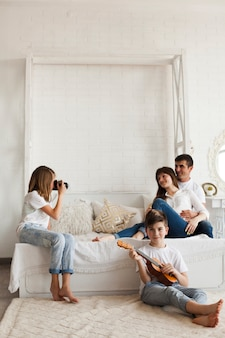 Girl taking photo of her parents and her brother playing ukulele at home
