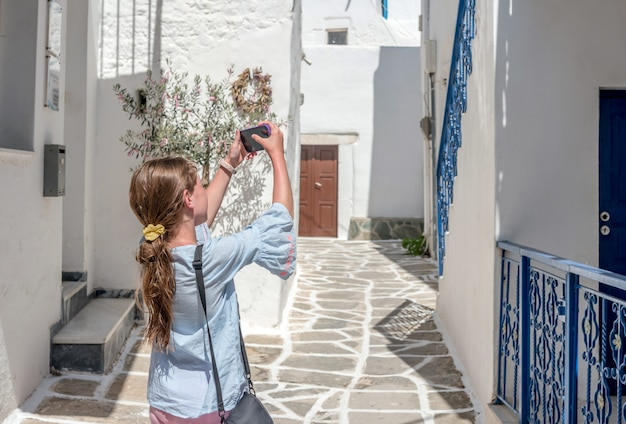 スマートフォンでギリシャの素朴な建築の写真を取っている女の子