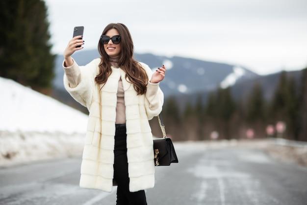 Девушка принимая фото ее собственной личности на smartphone на горах зимы