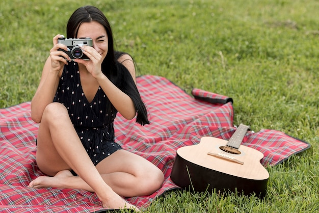 Girl taking a photo on picnic blanket