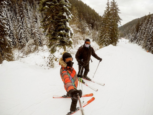 Girl taking photo with a selfie stick while skiing with a young man in a woods.