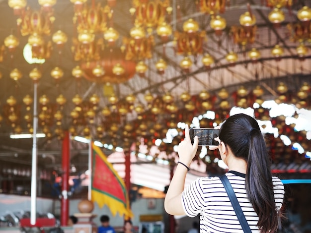 Girl taking photograph from mobile phone at china shrine.