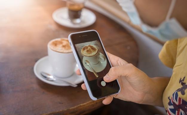Девушка фотографируя чашка кофе
