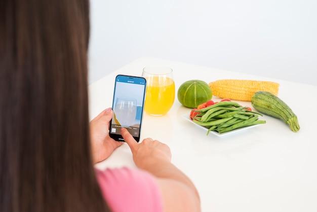 Девушка фотографируя овощ