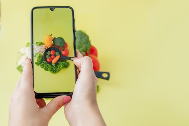 Girl taking picture of vegetarian food with her smartphone