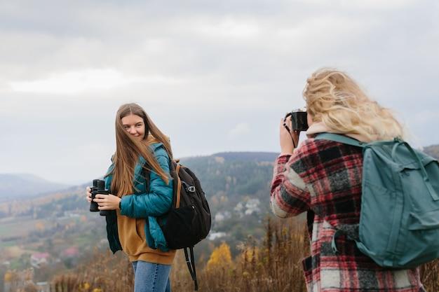 ハイキング中に山で友達の写真を撮る女の子