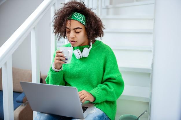 錠剤を服用している女の子。ノートパソコンを持って階段に座って熱いお茶を飲むファッショナブルな格好良い女性