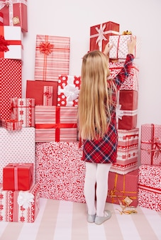 Девушка берет подарок из кучи