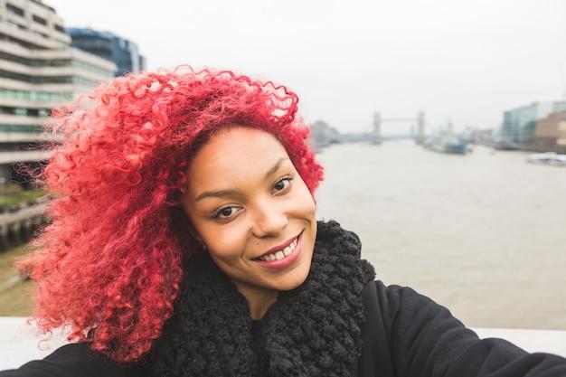 Girl taking selfie in london with tower bridge