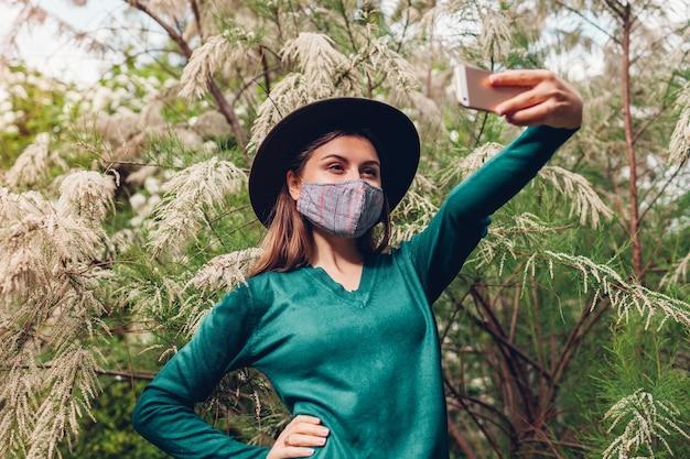 ブルーミングガーデンでの携帯電話でselfieを取っている女の子。屋外の防護マスクを着ている女性
