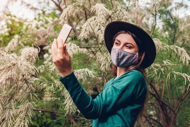 ブルーミングガーデンのスマートフォンでselfieを取っている女の子。屋外の防護マスクを着ている女性