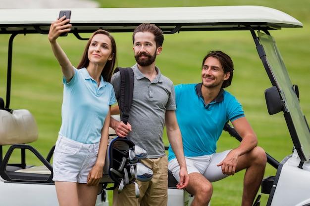 Девушка принимая селфи с друзьями на поле для гольфа