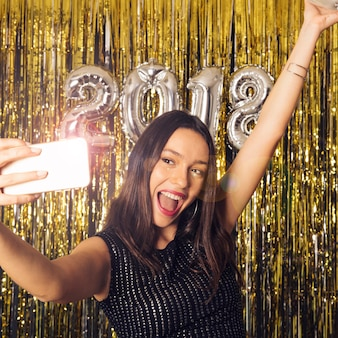 Girl taking selfie with shiny smartphone on new year celebration