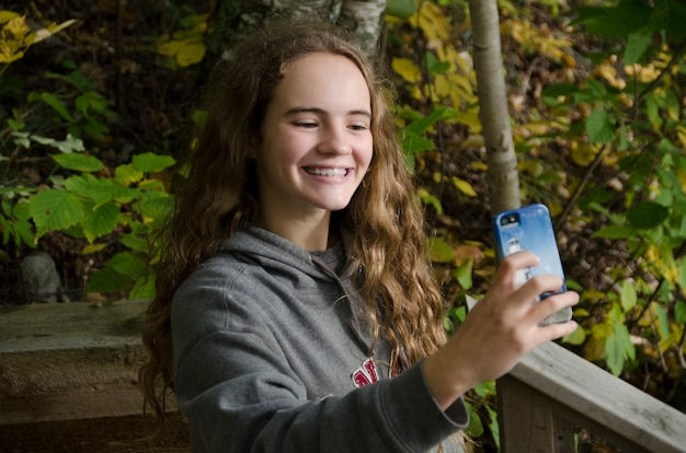 Girl taking selfie with a smartphone, lake of the woods, ontario, canada