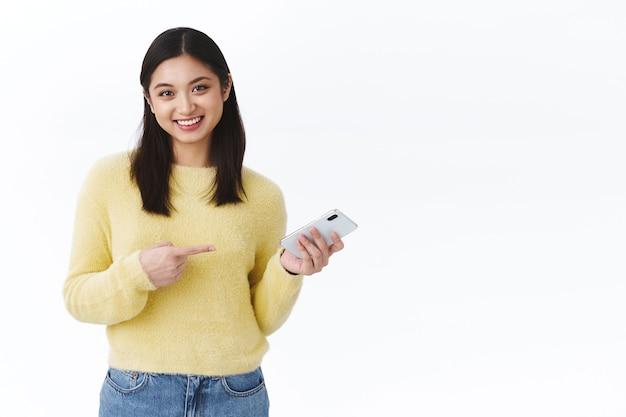 この男について話している女の子は、笑顔で友達と話しているときにオンラインで携帯電話を指さしているのを見つけました。スマートフォンを保持し、電話アプリケーションを促進する陽気なアジアの女性