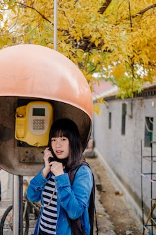 Girl talking by public telephone