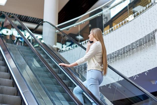 에스컬레이터를 등반하는 쇼핑몰에서 전화 통화하는 여자
