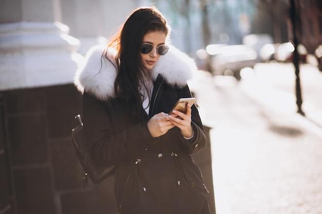 ビジネスセンターで通りの電話で話す少女