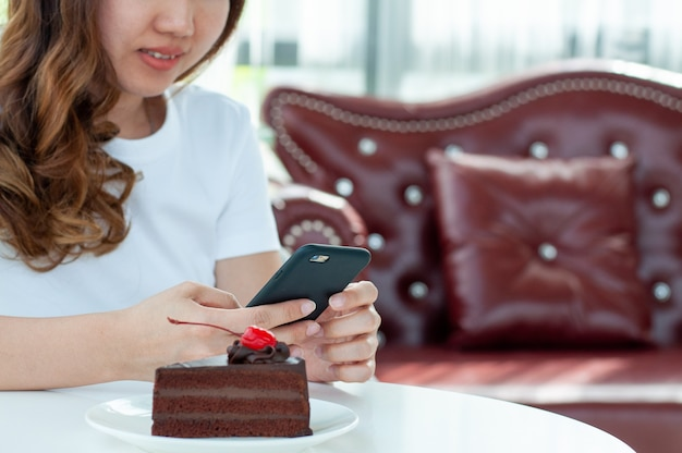 A girl talking online via mobile phone video sitting in a coffee shop. the concept of wireless connection to networks and modern technology