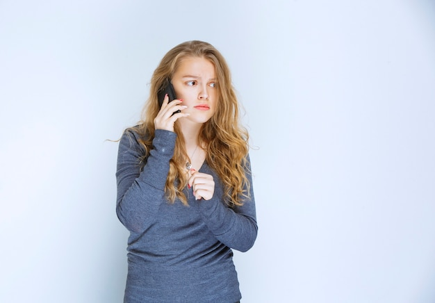 Girl talking to the phone and looks terrified.