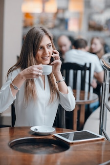 Girl talking on the phone while having coffee